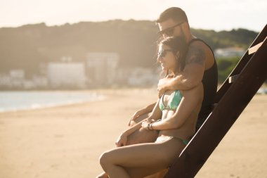 Romantic couple in hug watching sunrise/ sunset together.Young man and woman in love hugging and enjoying day at the beach.Flirting on summer vacation.Watching horizon,waves