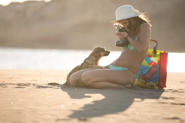 Young woman playing with dog pet and photographing on beach during sunrise or sunset.Girl and dog having fun on seaside