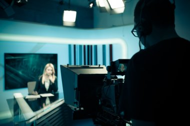 Young beautiful blonde television announcer at studio during live broadcasting.Female TV director at editor in studio.Recording at TV studio with television anchorwoman