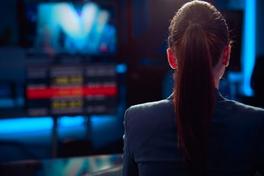 Television anchorwoman at studio during live broadcasting.Young beautiful television announcer at studio during live broadcasting