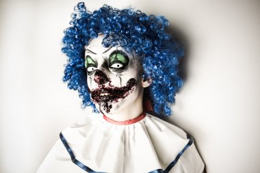 A closeup of a scarier clown with sharp pointy teeth glaring at you. Crazy ugly grunge evil clown on Halloween