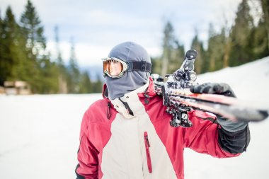 Young man holding ski at ski resort.Skier holding skis looking at the mountains.Side view of handsome skier man with mask and holding ski equipment