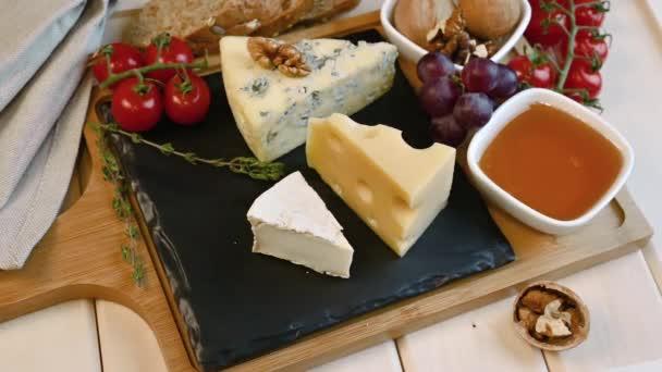 ručně položí nůž na stůl se sýrovou maasdam, ořechy, medem, hrozny a rajčaty na dřevěnou desku a podnos. sýrový talíř s nožem.