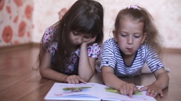 Zwei kleine Mädchen Schwestern auf dem Boden liegend ein Buch lesen