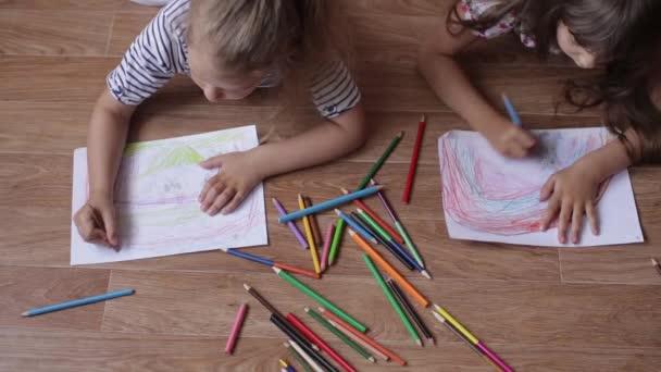 Fiatal ikrek testvérek rajz papír, színes ceruza, feküdt a padlón.