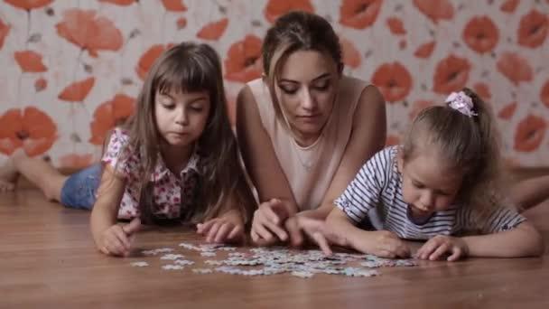 dvě malé dívky sestra shromažďuje hádanky s mámou, ležící na podlaze