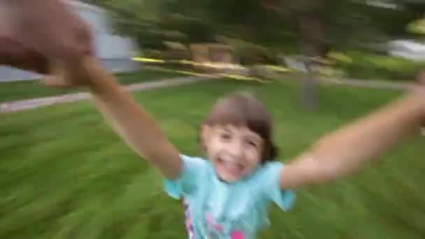 Young girl spinning around in parents hands, Kid Smiling at Camera