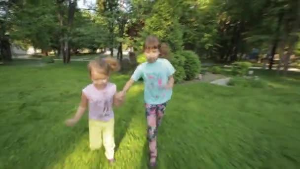 dvě malé holčičky běží trávou, drželi se za ruce. děti tráví čas venku