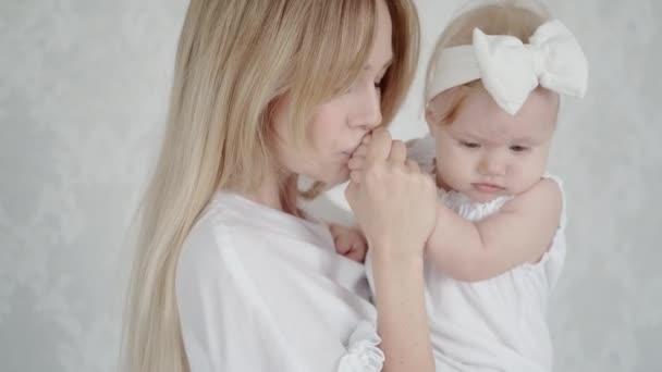 Mladá matka drží svou milovanou dceru v náručí a líbá ji. Portrét roztomilého dítěte a její matky. Úsměv dítěte. Světlé barvy