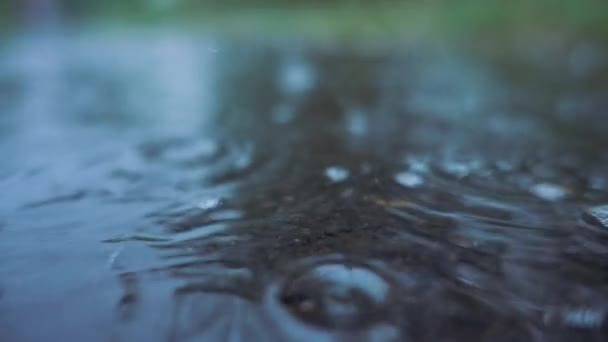 Raindrops falling on the ground in slow motion