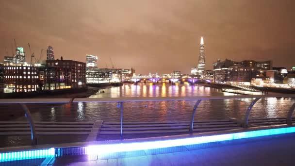 The Skyline of London from Millennium Bridge by night panning shot  - LONDON, ENGLAND