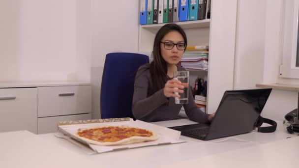 Young woman eats a pizza from delivery service while at work