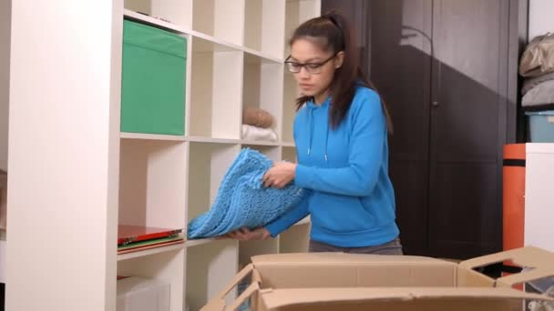 Young woman on the move carries a cardboard box