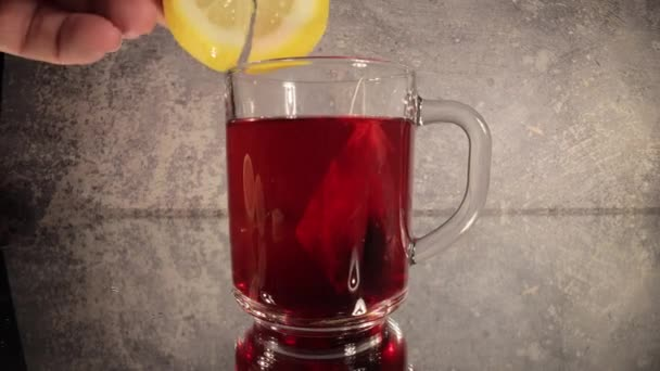 Adding a slice of lemon to a glass of tea