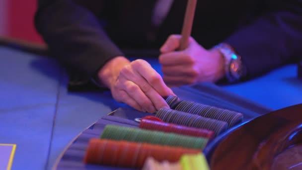Roulette-Tisch in einem Casino - groupier packt Spiele-Token