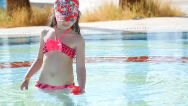 beautiful little girl playing with a flower in the pool