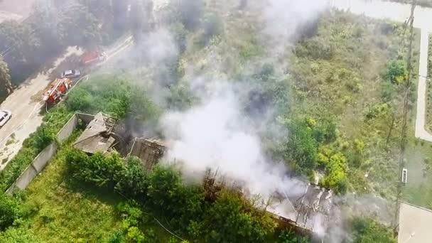 Dům je v plamenech - hasiči uhasit oheň s vodou. Letecký