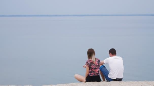 milenci sedí na břehu řeky