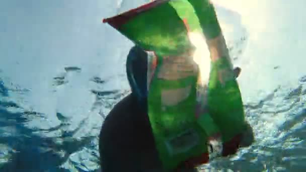 garbage collection in the sea or ocean. man, wearing a snorkeling mask, swims and collects trash thrown in water. close-up. sea, ocean pollution. environment protection,