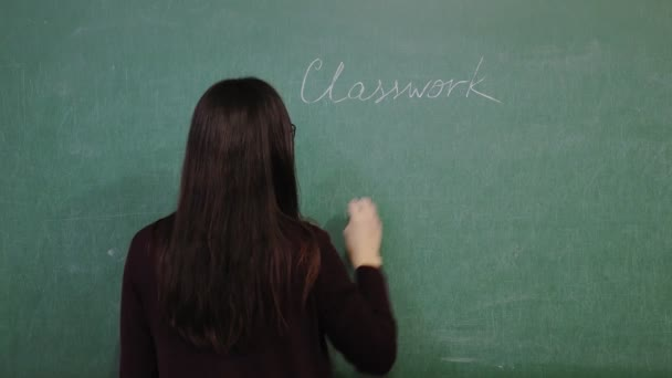 Online schooling. teacher is explaining material during online math lesson. She is writing rules, formulas with chalk on blackboard, in school class. remote teaching. live video streaming from class.