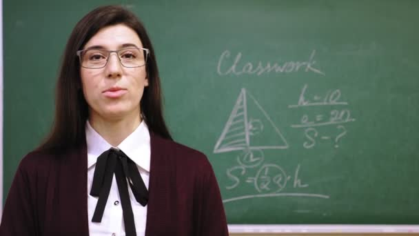 Online schooling. Female teacher is holding online math lesson in school class. blackboard backdrop with written rules, formulas on it. remote teaching. live video streaming from class.
