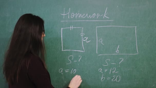 Online schooling. Female teacher is holding online math lesson. She is writing rules, formulas with chalk on blackboard, in school class. remote teaching. live video streaming from class.