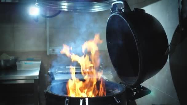 vaření. vaření hamburgerů. pohled zblízka. Hot, open fire gril gril v kuchyni restaurace. plameny a kouř ve zpomaleném filmu. rychlé občerstvení, nezdravé jídlo,