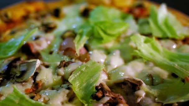 vaření. Dělám pizzu. Detailní záběr. Mňam, šťavnatá, čerstvě připravená, horká pizza s listovým salátem, bylinkami, navrch. proces vaření italské pizzy .