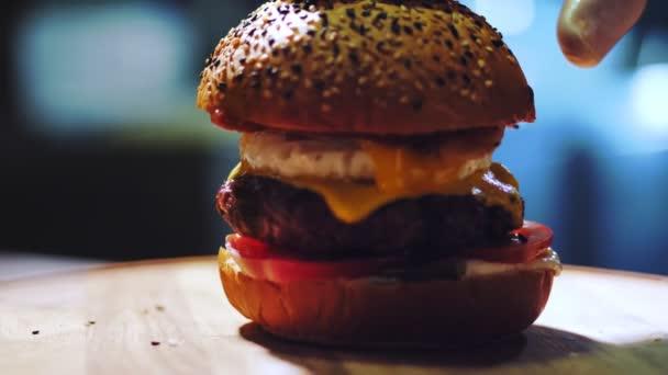 vaření hamburgerů. Detailní záběr. Velký chutný burger s čerstvými okurkami, rajčaty, šťavnatým, grilovaným hovězím koláčem se sýrem a smaženým vejcem. rychlé občerstvení, nezdravé jídlo.