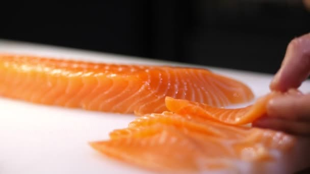 Hagyományos japán étel. Sushi előkészítés. Közelkép. Sushi séf friss lazacfilét szeletel késsel egy fehér vágódeszkán a sushi bárban. Sushi nigiri halat készítek. Japán konyha receptek.