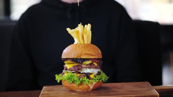 Hamburger, burger. detailní záběr. číšník nalévá omáčku na šťavnatý, chutný, čerstvě udělaný burger s hranolkama. rychlé občerstvení, nezdravé jídlo.