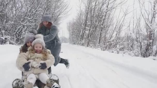 Familienrodeln im Winter. Winteraktivität im Freien. Glückliche, lachende Familie, Frau mit 2 Töchtern genießen das Rodeln auf der verschneiten Straße, im Wald, bei Schneefall. Familie hat Spaß, gibt Geld aus