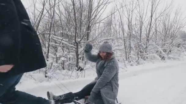 Familienrodeln im Winter. Winteraktivität im Freien. Glückliches, lachendes, verspieltes Ehepaar genießt das Rodeln auf verschneiter Straße, im Wald, bei Schneefall. Sie haben Spaß, verbringen Zeit miteinander