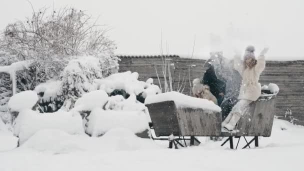 Familienspaß im Winter. Schnee werfen. Glückliche, lachende, verspielte vierköpfige Familie genießt Schnee und Schneefall, hat Spaß und verbringt Zeit miteinander an einem verschneiten Wintertag. Zeitlupe