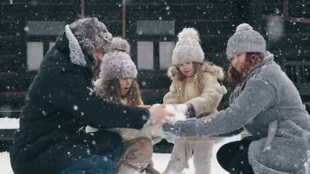 zimní rodinná zábava. dělá sněhové koule. Šťastná čtyřčlenná rodina si užívá sněhu a sněžení, baví se venku, tráví spolu čas na zasněženém zimním dni. zpomalený pohyb
