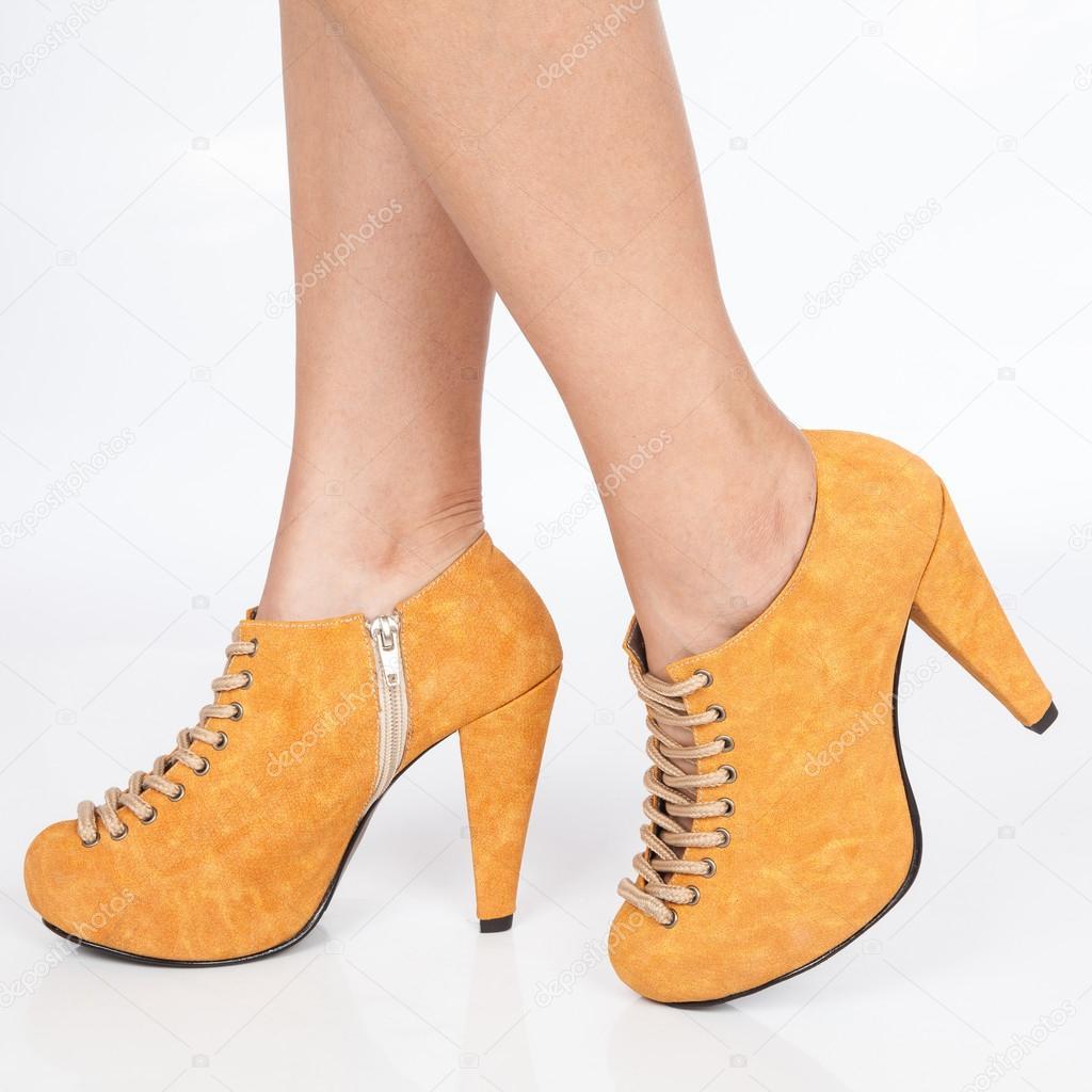 Πόδια της γυναίκας με τα τακούνια παπούτσια πορτοκαλί με κορδόνια μπεζ σε  λευκό φόντο — Φωτογραφία 4103df46246