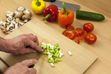 Close up of a chefs hands chopping some salad onions
