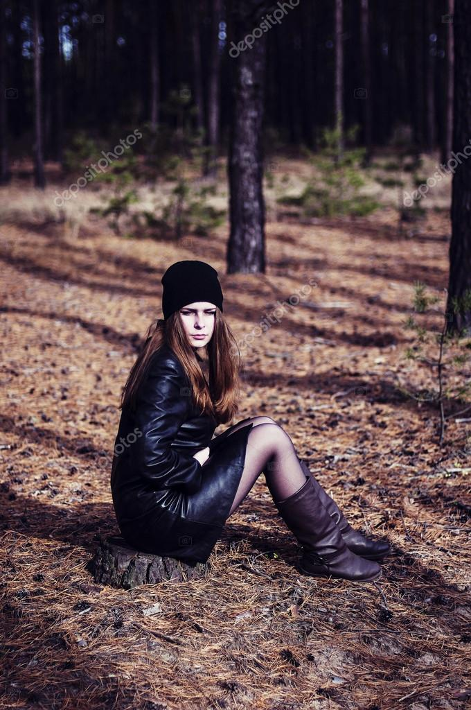 The girl in a black leather coat and a black hat standing , hold