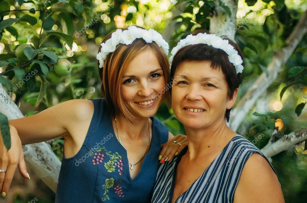 Portrait of a smiling mother and daughter are posing in wreaths of artificial flowers from the outdoors on a background of trees. The concept of family. The relationship of the mother and daughter.