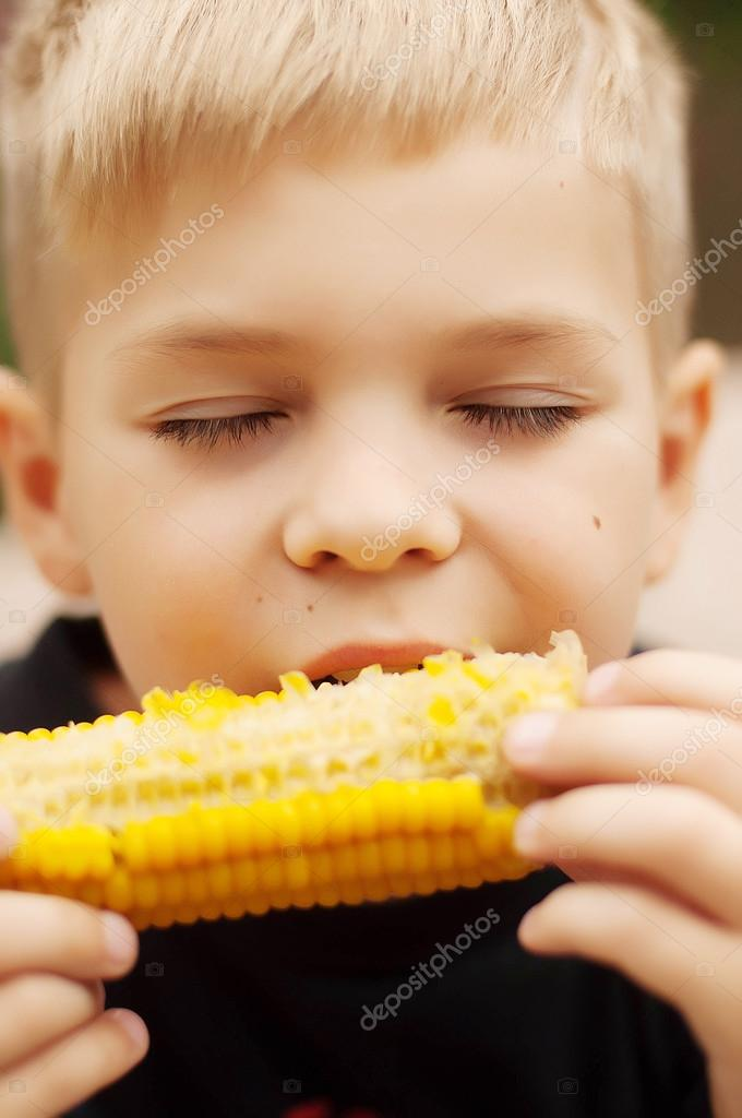 Young boy with  corn on the cob in the backyard. A  boy happy ab