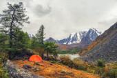 Kempování na podzimní náhorní plošině. Pomerančový stan pod deštěm. Klid a relaxace v přírodě. Horní Shavlin Lake v Altai.