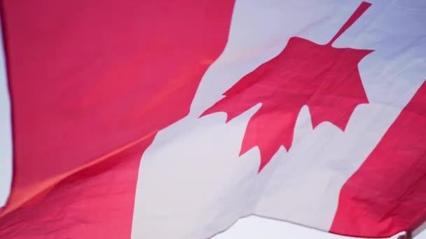 Die Flagge von Kanada. Nationales kanadisches Symbol in den Händen einer Person im Wind