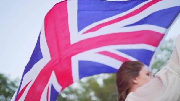 Dosažení cíle a úspěchu ve Spojeném království. Student s anglickou vlajkou v rukou