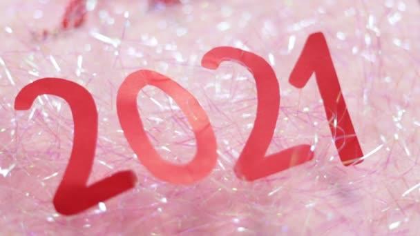 Inschrift 2021 auf Lametta. Zahlen 2021 aus rotem Papier auf rosa Hintergrund. Neujahrsvideo