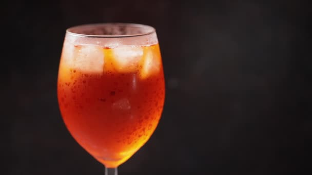 Barkeeper legt eine Orangenscheibe in einen Cocktail. Cocktail Aperol Spritz auf schwarzem Hintergrund. Ein Glas orangefarbener Sommercocktail. Zeitlupe. Kopierraum