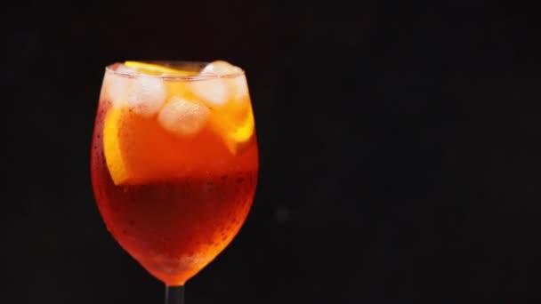 Cocktail Aperol Spritz rotiert auf schwarzem Hintergrund. Sommerorangefarbener Cocktail im rotierenden Glas. Drehen. Kopierraum