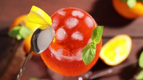Aperolspritz mit Cocktaillöffel. Cocktail Aperol Spritz mit Orangenscheiben, Eis und Minze. Kamerabewegung rund um das sommerliche Cocktailglas