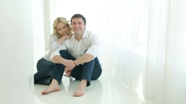Husband and wife sitting on the floor next to each other near a large window, they hug, looking at the camera. Bright room with light curtains. Happy family in white shirts and jeans. Man and woman smiling.