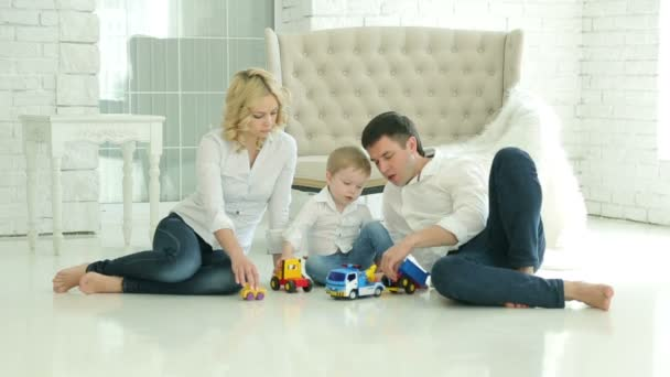 Mom dad and son on the floor. Son playing toy car. Happy European family. On the background of white floor and sofa, a window and white brick walls