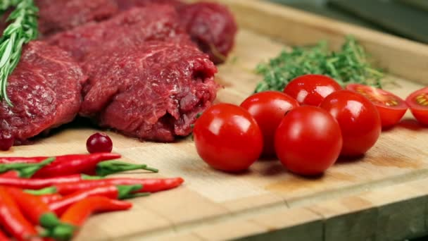 Čerstvé maso na steak na dřevěné desce. Mramorované maso, hovězí maso. Poblíž rajčata, rozmarýnu, tymiánu, citron, červený pepř, brusinky. Kuchař nalévá brusinky na šachovnici, přidává maso rozmarýn.